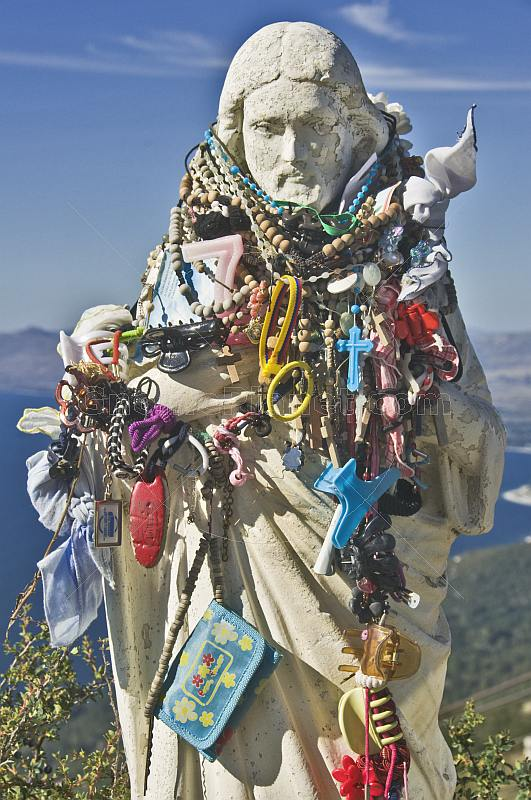 Statue of Christ with good-luck charms and wishes hung for blessings.