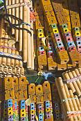 Pan pipes and wooden whistles for sale on a souvenir stall.