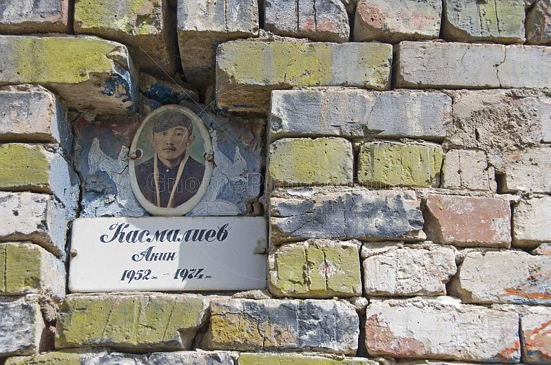 A Kyrgyz brick-built tomb with photo-nameplate in a lonely graveyard.