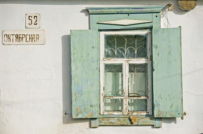Whitewashed cottage wall and green window frame.