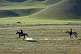 Two Kyrgyz horsemen riding at a canter over sparse grassland.