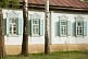 Russian-style painted Cottage with shutters, decorative windows and surrounding Birch Trees.