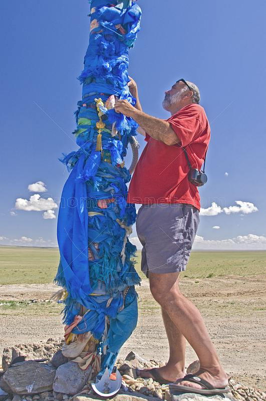 Tying a blue prayer scarf on an 'Ovoo', a Mongolian Shamanistic cairn for travellers.