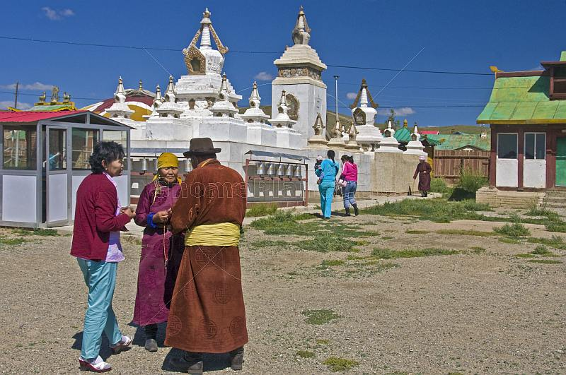 An elderly Mongolian couple in traditional dress talk after the service at the Gandan Muntsaglan Khiid monastery.