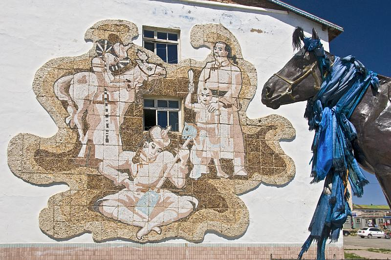 Mongolian cultural wall mosaic and horse statue with prayer scarves.