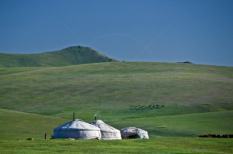 Three yurts on the grassy slopes of the mountains.