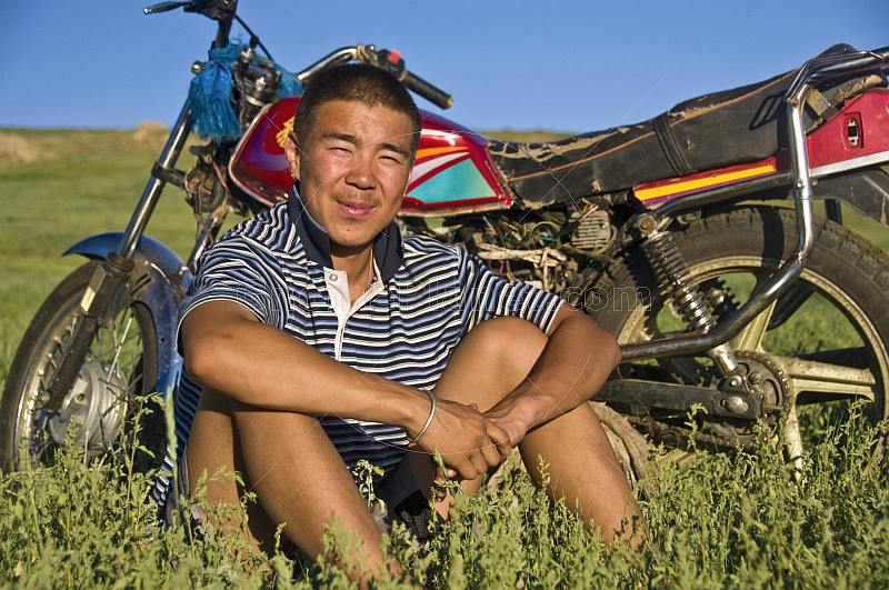Mongolian man with motorbike in the wide open pasture-land of the Mongolian steppe.