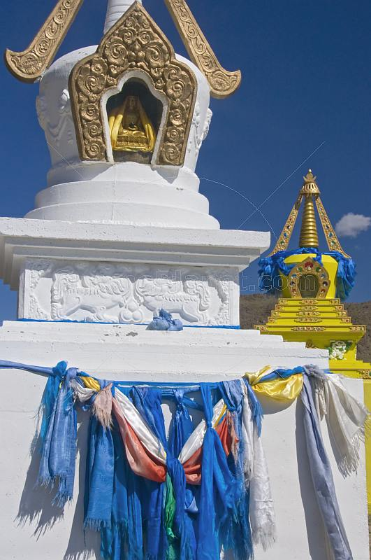White and yellow Dagobas with blue prayer scarves at the Singino monastery.