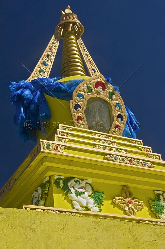 Yellow Dagoba with blue prayer scarves at the Singino monastery.