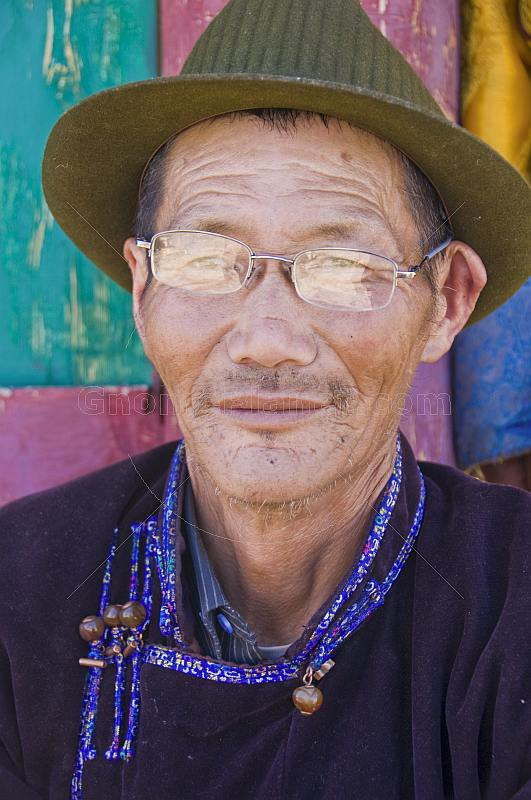 Mongolian carpenter in hat and traditional buttoned jacket.