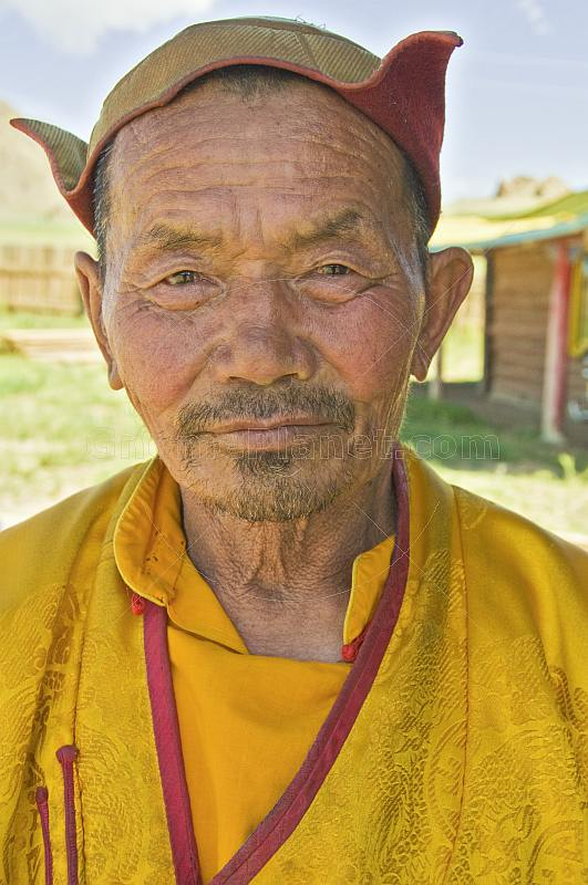 Mongolian carpenter in hat and traditional yellow jacket.