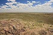 Rocks and low hills rise above the bare Mongolian plains.