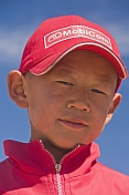 Small Mongolian boy in a red hat and jacket.