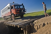 Dragoman Overland truck crossing a rickety wooden bridge.