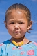 Small Mongolian girl in a blue top and yellow beads.