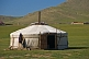 A Mongolian yurt with open door, in a field.