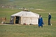 Image of Mongolian man and boy stand next to their yurt.