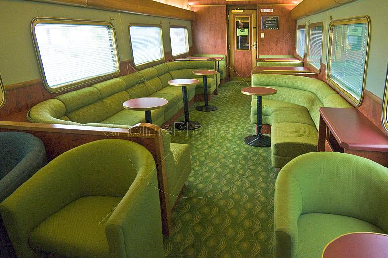 Tables and seating in the Red Gum Lounge Car of the Ghan long distance train.