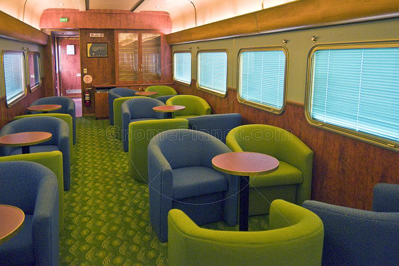 Tables and armchairs in the Red Gum Lounge Car of the Ghan long distance train.