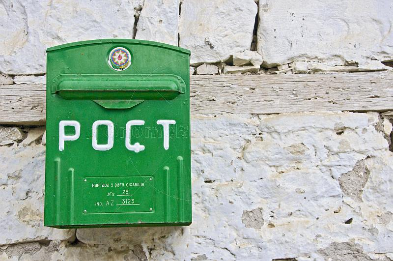 Green post-box on a whitewashed wall.
