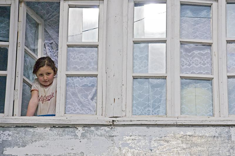 A young girl in a California teeshirt looks out of the window of her village house.