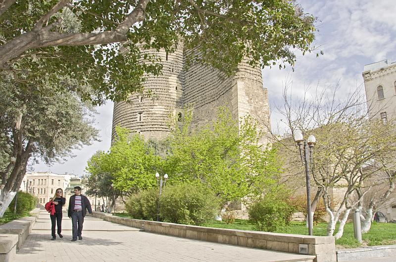 A young couple walk past the 29m high 12thC 'Qiz Qualasi' or Maidens Tower.
