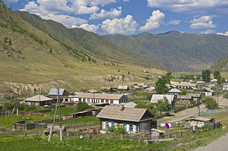Small Russian village of log houses nestles between the Altai Mountains.