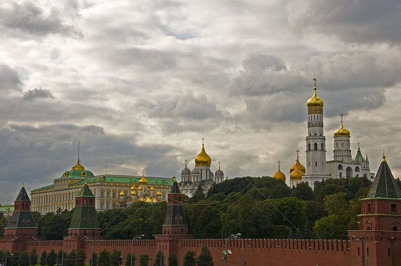 The golden domes and green copper roofs of the Kremlin contrast a cloudy sky.