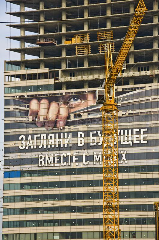 Skyscraper under construction covered by a large poster.