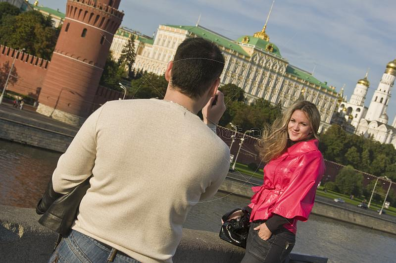 Russian tourists photographing in front of the Kremlin, on the Moscow River .