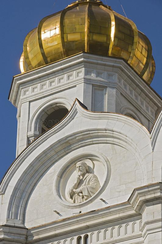 Detail of stone carving and gold dome on the Cathedral of Christ the Saviour which stands next to the Moscow River.