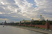 The golden domes and green copper roofs of the Kremlin along the Moscow River contrast a cloudy sky.