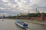 A sight-seeing boat on the Moscow River passes the red walls of the Kremlin, under a cloudy sky.