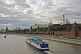 Image of A sight-seeing boat on the Moscow River passes the red walls of the Kremlin, under a cloudy sky.