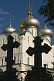 The sharp black silhouettes of two tombstones in the shape of crosses contrast the gold crosses on the Smolensk cathedral at the Novodevichy Convent.