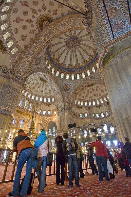 Tourist group views the domed interior of the Sultan Ahmet Camii, the Blue Mosque, in Sultanahmet.