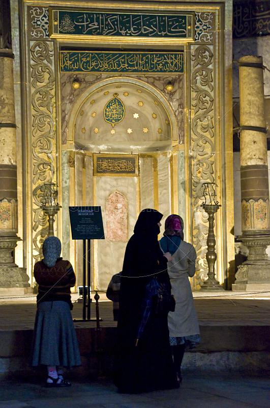 Three female pilgrims view the mihrab of the Aya Sofya in Sultanahmet.