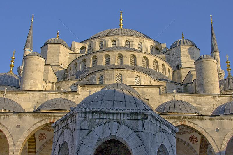 Domes of the Ahmet Camii Blue Mosque lit by evening sunshine.