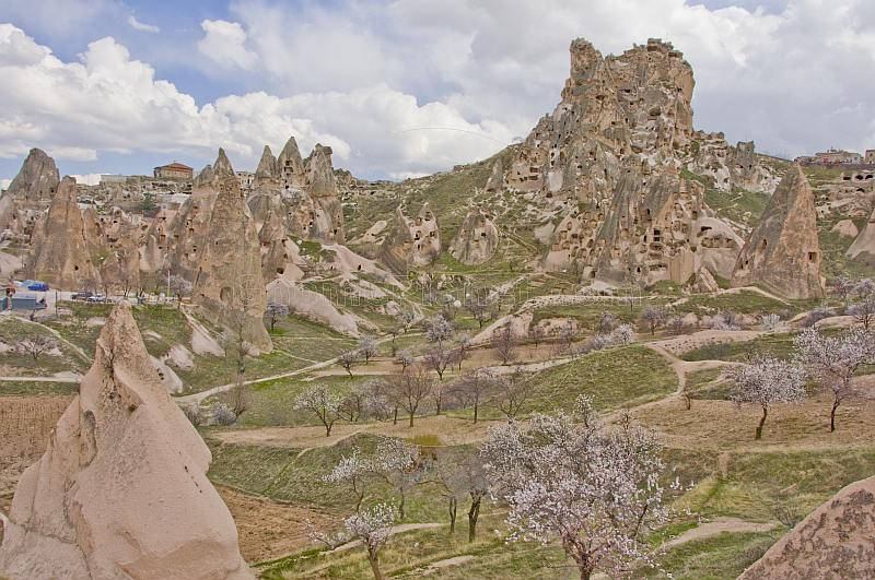 The dramatic rock castle dominates the blossomed valley of tuft dwellings.