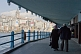Elderly couple walk on lower deck of the Galata Bridge, to cross the Golden Horn.