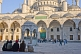 Worshippers wait in the courtyard of the Ahmet Camii Blue Mosque lit by evening sunshine.