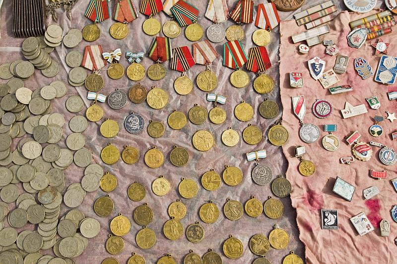 Coins, badges, and Soviet medals for sale at the Tolkuchka Bazaar.