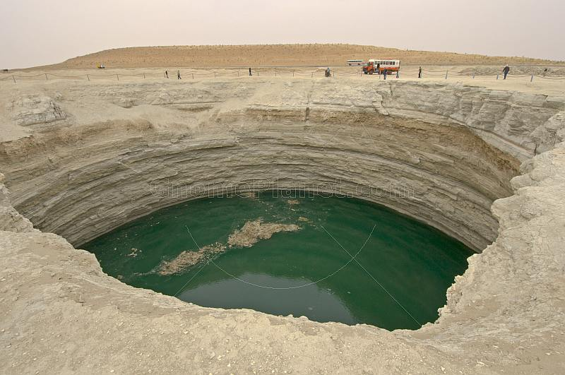 A Dragoman overland truck is dwarfed by the Darvaza Water Crater.