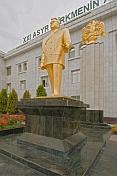 Golden statue of President Niyazov outside a government building.