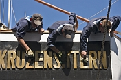 Young Russian cadets clean the brass nameplate of the sailing ship 'Kruzenshtern'.