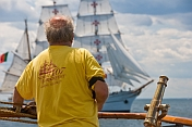 Mariner on the quarterdeck of the 3 masted barque 'Picton Castle' watches the tallship 'Sagres' pass by.