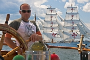 Man at the wheel of the 3 masted barque 'Picton Castle' with tallship 'Sagres' in background.
