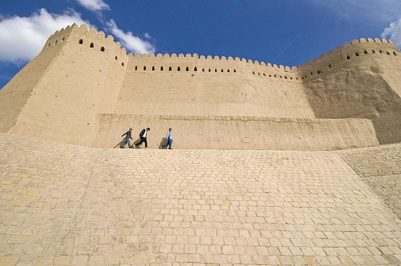 Three schoolboys walk in front of the city walls.