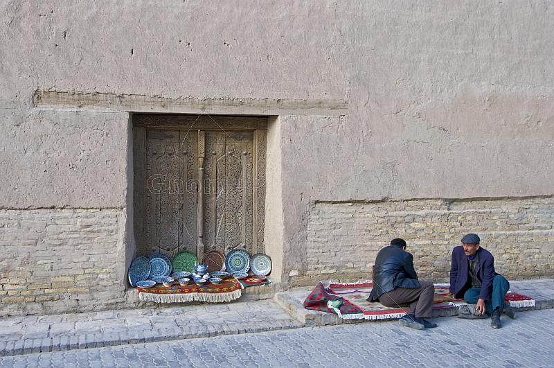 Two Uzbek traders wait for customers to visit their display of ceramics.