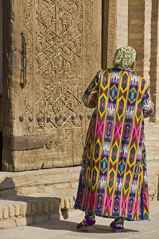 Elderly Uzbek lady in traditional hand dyed silk Chopon coat, stands before an intricately carved wooden door.